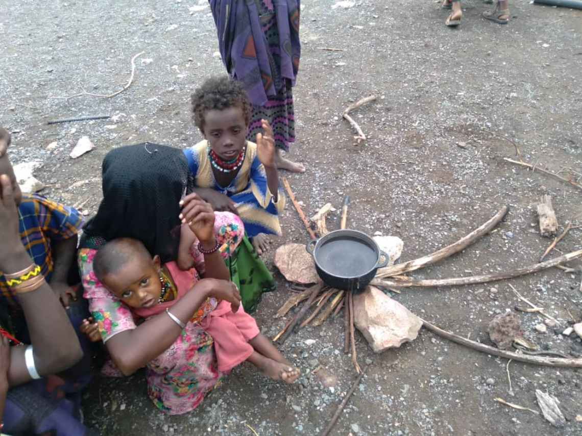 Displaced family boiling water in schoolyard