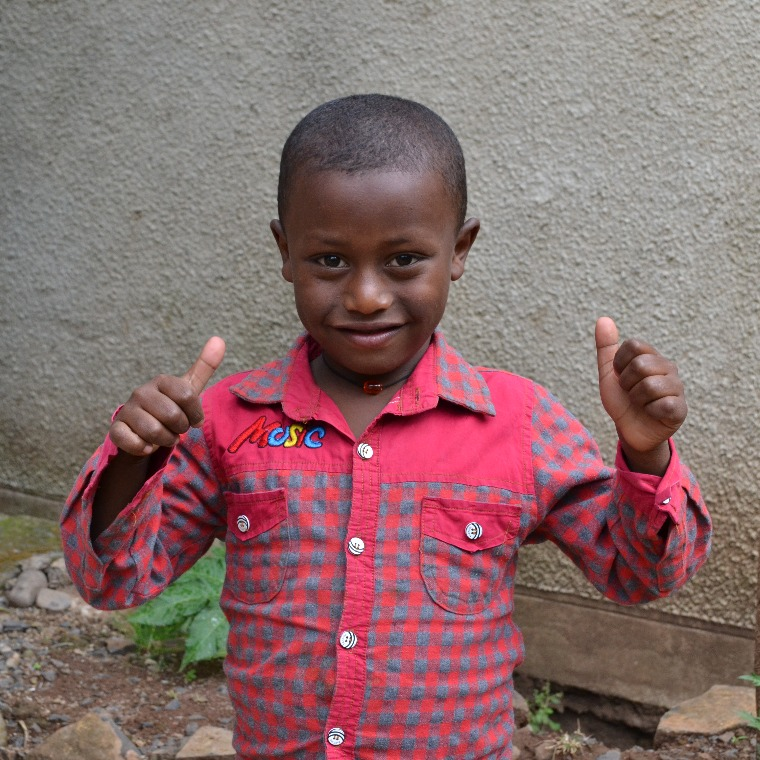 Young Ethiopian boy gives thumbs up. His group children's home is supported by your monthly giving to Ethiopia