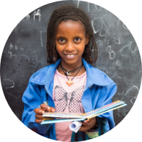 Young Ethiopian girl holding a book in classroom - a gift in your Will to charity can improve education opportunity in Ethiopia